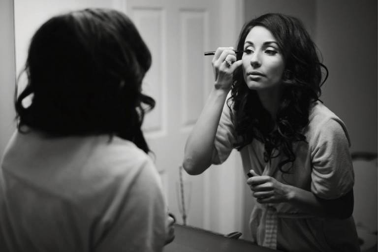 Bride at mirror getting ready in black and white